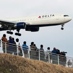 FILE - In this March 14, 2015, file photo, people watch a landing Delta Air Lines jet approach the Narita International Airport from a popular viewing spot at Sakuranoyama Park in Narita, east of Tokyo.