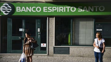 Two persons stand in front of an agency of BES (Espirito Santo Bank) bank in Lisbon on August 1, 2014.