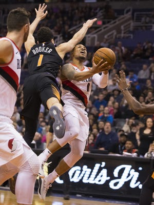 Trail Blazers Damian Lillard (0) hits a game-winning layup against Suns Devin Booker (1) during the second half at Talking Stick Resort Arena on February 24, 2018 in Phoenix, Ariz.