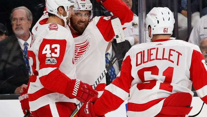 Red Wings left wing Darren Helm, left, celebrates with center Henrik Zetterberg, center, after Zetterberg scored against the during the second period on Friday, Oct. 13, 2017, in Las Vegas.