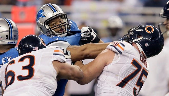 Detroit Lions defensive tackle Ndamukong Suh tangles with Chicago Bears center Roberto Garza (63) and guard Kyle Long (75) during the first half the Thanksgiving game.