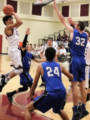 Tularosa's Marcos Barreras, left, attempts a jump shot while under heavy pressure.