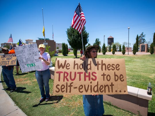 Diane Alfaro, center, holds a sign at the Stand By Me for Liberty rally at Alameda Park in Alamogordo, July 9, 2016. Alfaro said she believed the country was taking a wrong turn and that the Bureau of Land Management was abusing rancher's private property rights.