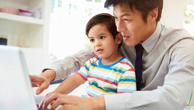 A father works from home with his son on his lap.