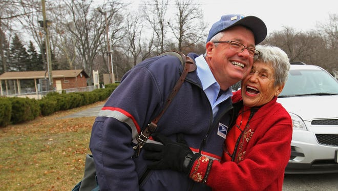 Mailman Tom McMahon of the Boonton Post Office, gets some affection from Lake Intervale resident Teena Skinner, who stopped to offer her gratitude to him. McMahon will be retiring soon after many years delivering mail to the same neighborhood in Parsippany, December 16 2014 Parsippany NJ.