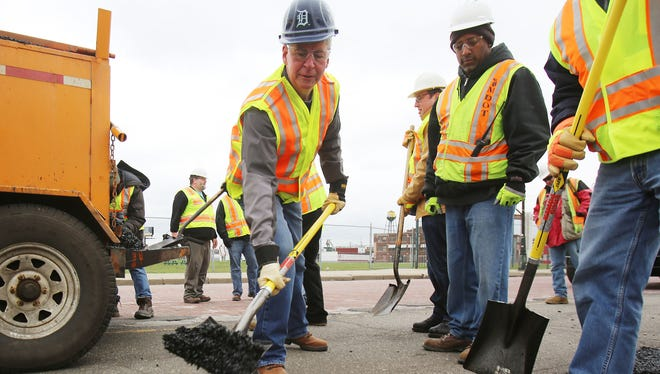 Gov. Rick Snyder , left,  assists MDOT workers along Michigan Ave. near Trumbull to patch potholes Thursday, April 23, 2015, in Detroit.
