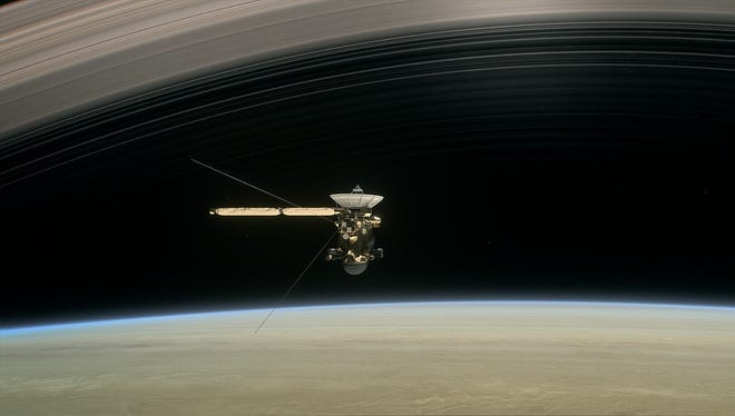 "This image made available by NASA in April 2017 shows a still from the short film ""Cassini's Grand Finale,"" with the spacecraft diving between Saturn and the planet's innermost ring. Launched in 1997, Cassini reached Saturn in 2004 and has been exploring it from orbit ever since."