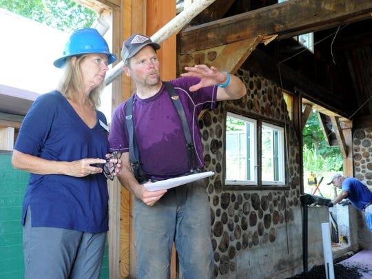 Blacksmith crew supervisor Matt Haugh shows Warren Wilson College president Lynn Morton the improvements being made to the blacksmith shop.