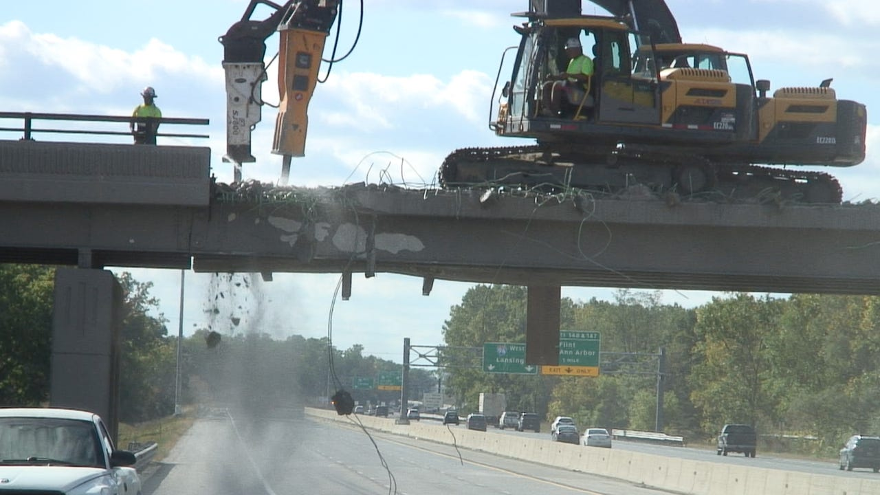 After a semi truck damaged the Pleasant Valley Road overpass, Michigan Department of Transportation begins demolition of the portion of the overpass over eastbound I-96 traffic.