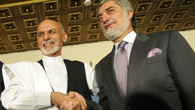 Afghan Presidential candidates Ashraf Ghani Ahmadzai, left, and Abdullah Abdullah shake hands during a press conference in Kabul, Afghanistan, on July 12, 2014.
