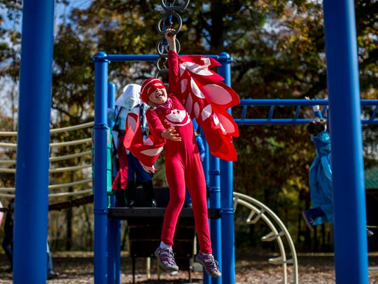 Quira Hollenbeck, 6, of Marysville, is dressed as a character from PJ Masks while playing on a playground during a trunk-or-treat Saturday, Oct. 22, 2016 at St. Clair Township Park.