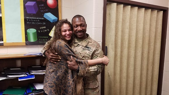 Sgt. Major Harrington Henry hugs his daughter Amaris Butler after surprising her by returning from his deployment to Afghanistan.