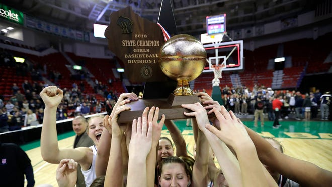 Appleton North High School's Sydney Levy, center, raises the championship trophy with her teammates after defeating Mukwonago High School in the Division 1 championship game at the 2018 WIAA state girls basketball tournament at the Resch Center in Ashwaubenon.