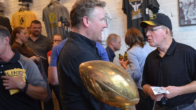 Fashion designer and Tailgate Clothing Company founder Todd Snyder, left, talks with former University of Iowa wrestling coach Dan Gable on Thursday at the new downtown shop.