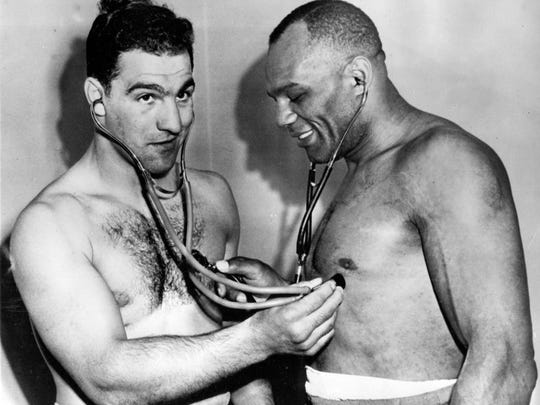 American Heavyweight Champion Rocky Marciano, left, and American challenger Jersey Joe Walcott, listen to each other's heart beats after a medical check in Chicago, on May 8, 1953, one week before their scheduled title fight.