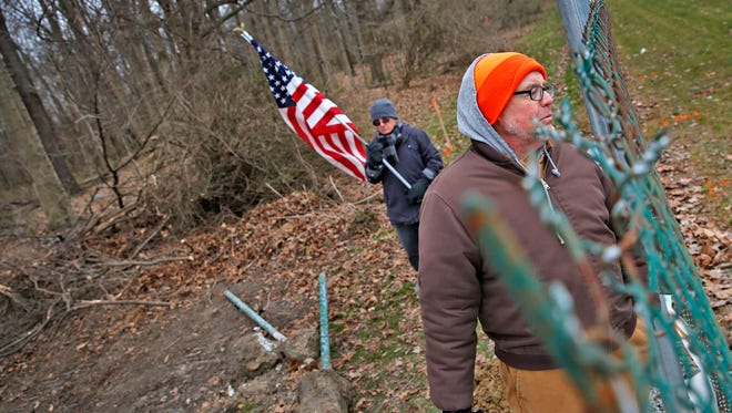 Gary Moody looks over the fence during a protest against an old-growth forest tree removal for a Veteran Affairs project, at Crown Hill Cemetery, Monday, March 13, 2017.