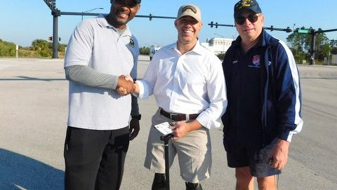 Robin Bynoe, left, Congressman Brian Mast, and Dayne Clemmer cheer on participants in the 2017 race planned by the Treasure Coast chapter of the Military Officers Association of America.
