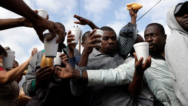 In this Oct. 3, 2016 photo, Haitian migrants receive food and drinks from volunteers as they wait in line at a Mexican immigration agency in Tijuana with the hope of gaining an appointment to cross to the U.S. side of the border. Many Haitians arriving at the Mexico-U.S. border are unaware of a new U.S. policy of putting them in deportation proceedings and detaining them while making efforts to fly them home.