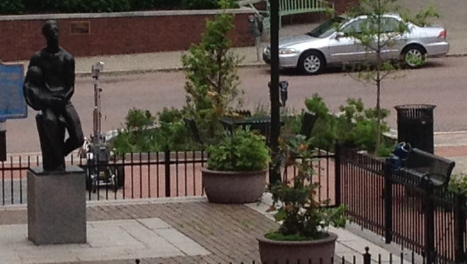 Police robot (left) is in action near suspicious package on bench (right) in Wilmington.