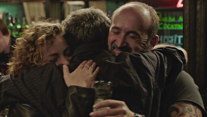 "Tomás (Javier Cámara) and Paula (Dolores Fonzi) hug Julián (Ricardo Darin) in ""Truman."""