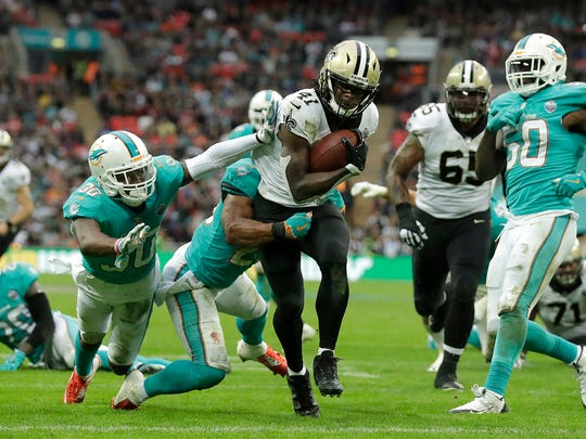 FILE - In this Oct. 1, 2017, file photo, New Orleans Saints running back Alvin Kamara (41) runs past Miami Dolphins defenders to score a touchdown during the second half of an NFL football game, at Wembley Stadium in London. Now that Adrian Peterson has been traded to Arizona, the Saints have a clearer vision for a running game that increasingly features rookie Alvin Kamara, and coach Sean Payton no longer has to answer questions about the Peterson's lack of usage in the offense.  (AP Photo/Matt Dunham, File)