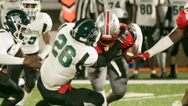 Jenkins High senior running back Damozzio Harris (carrying the football) is met by Windsor Forest's DeMarquez London (26) during first-quarter action Thursday night at Memorial Stadium. Windsor Forest won 14-6.