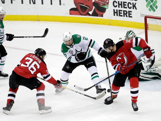 New Jersey Devils right wing Nick Lappin (36) gets his shot through the defense of Dallas Stars defenseman Stephen Johns (28) and goalie Kari Lehtonen (32), of Finland, for a goal as teammate right wing Jimmy Hayes (10) looks on during the third period of an NHL hockey game, Friday, Dec. 15, 2017, in Newark, N.J. (AP Photo/Julio Cortez)