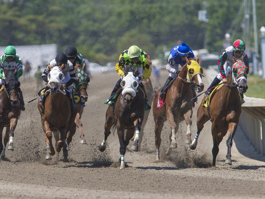 Horses round the clubhouse turn at Monmouth Park on opening day in 2016.