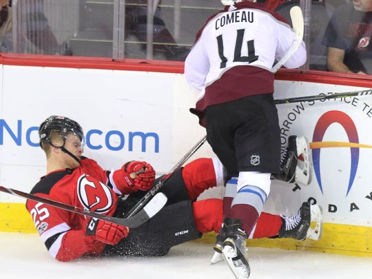 Mirco Mueller of the Devils is checked by Blake Comeau