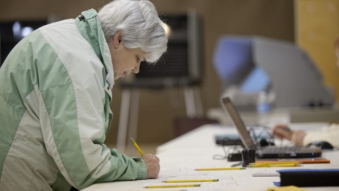 Ann Burns fills out a voting application before voting at St. Clair City Hall.