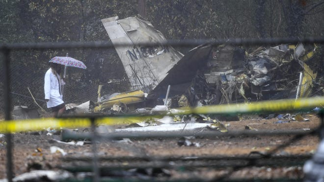 A person investigates the scene of a small plane crash in a city park which killed all on board, Thursday, Dec. 20, 2018, in northwest Atlanta.