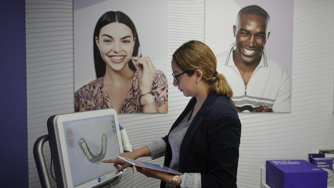 Dental assistant Jessica Buendia looks at a scanned image of patient's teeth in SmileDirectClub's SmileShop located inside a CVS store Wednesday, April 24, 2019, in Downey, Calif. CVS Health is venturing into dental care with plans to offer the relatively new teeth-straightening service.