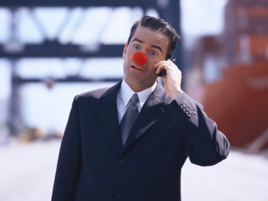 portrait of a businessman wearing a rubber ball nose and talking on a mobile phone