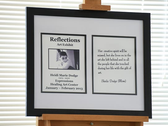 A photo of Heidi Dodge sits by her artwork Thursday,