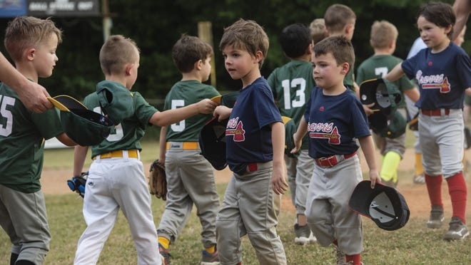 Members of the Braves T-ball team tap their hats with members of the Athletics team instead of giving high-fives in order to avoid physical contact at the end of a baseball game on June 15 in Tyler. The Rose Capital East Little League teams held their first games earlier this month, after a delay in the season due to COVID-19.