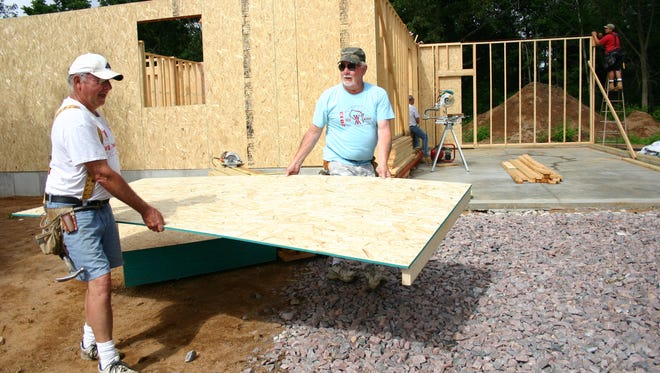 Jim Zwicke (right) works on the 2016 Habitat for Humanity house recently, alongside other volunteers and the Gonzalez family.