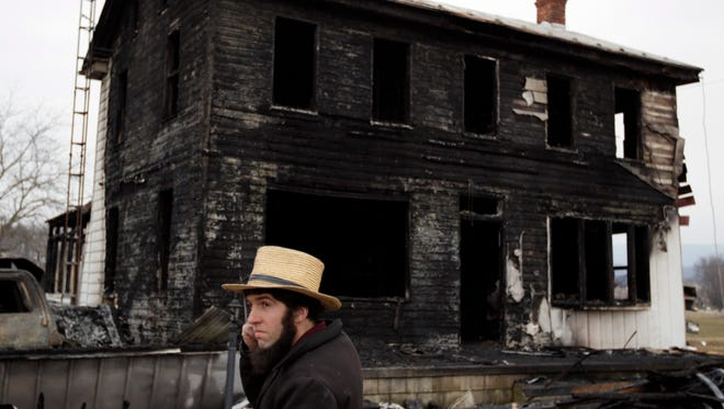 A neighbor stands near the fire ravaged farmhouse of Theodore and Janelle Clouse Wednesday, March 9, 2011, in Perry County. Seven Clouse children  perished in a fast-moving fire.