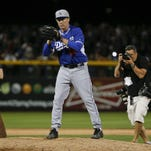 Actor Will Ferrell warms up for his pitching stint for the Los Angeles Dodgers during a spring training baseball game between the San Diego Padres and the Los Angeles Dodgers Thursday, March 12, 2015, in Peoria, Ariz.