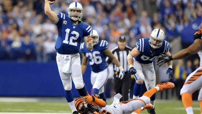 Indianapolis Colts quarterback Andrew Luck (12) is pressured by Cincinnati Bengals defensive end Carlos Dunlap (96)