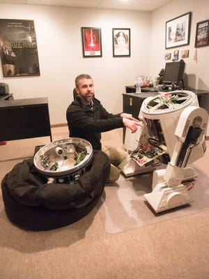 """Surrounded by Star Wars movie posters in his Ohio basement, Josh Montgomery, who calls himself the """"ultimate geek,"""" demonstrates the inner workings of his R2D2 robot and the computers that are used to make him fully functional."""