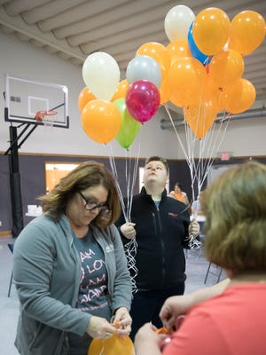 Raven Swearingen, middle, holds balloons handed to him by Tina Fulton as they were being blown up to be released later Sunday to honor the Rhoden family on April 22, 2018, two years after the tragic murder of the Pike County family.