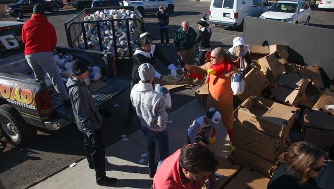 Volunteers and employees of Adams Construction and Management pull frozen turkeys from boxes and load them into trucks for delivery to local food banks Thursday, Nov. 20, 2014 in St. George.
