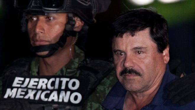 """Mexican drug lord Joaquín """"El Chapo"""" Guzmán, right, is escorted Jan. 8 by soldiers and marines to a waiting helicopter at a federal hangar in Mexico City."""