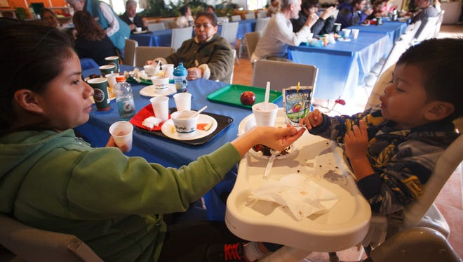 Araceli Bernal, left, feeds a strawberry to her young son, Jesse as he sits in a high chair  during the Dixie Care and Share Community Soup Kitchen lunch at Grace Episcopal Church Friday, Jan. 24, 2014.
