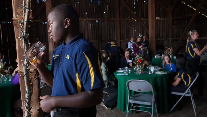 "William Penn senior Malcholm Washington, 17, and other students gather for a celebration of the success of Penn Farm in 2014. The high school's farm to school program is being recognized as a ""Superstar in Education"" this year by the state Commerce Chamber."