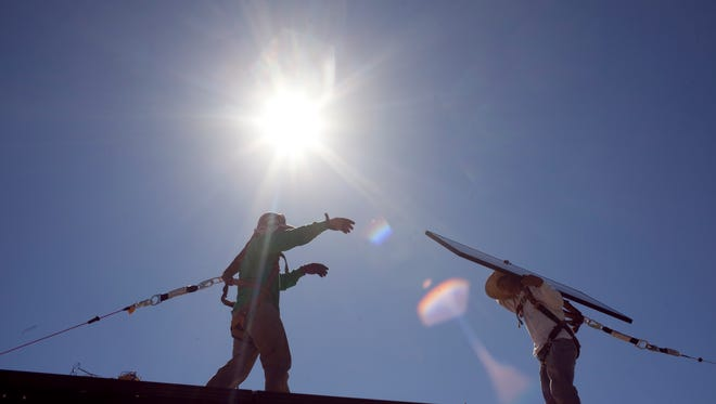 SolarCity employees install a 170-watt solar panel on the roof of a north Phoenix home in 2010.