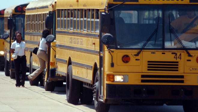 Students board school buses in this file photo