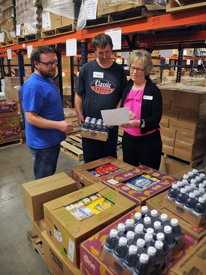 Kara Nickens, CEO of the Wichita Falls Area Food Bank, talks with Operations Director Rusty Williams, left, and volunteer Michael Horton in the warehouse in this file photo. The food bank received two grants totalling $40,000 which they will use to match funds donated by the community in the month of December.