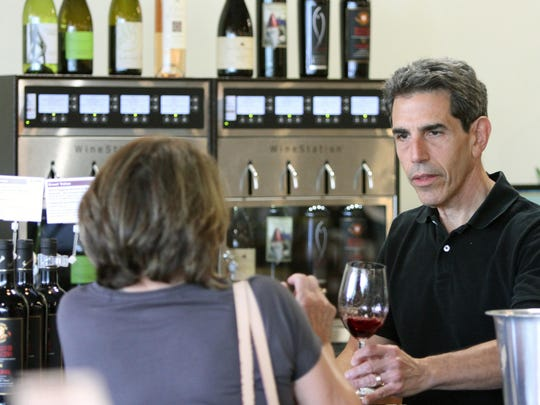 Gary's Wine & Marketplace in Hillsborough, a roughly 9,000 square-foot store which features a broad selection of wines, craft beers, and spirits, and gourmet cheeses, crackers, olives, and charcuterie as well as related gifts and accessories is photographed on Tuesday June 30, 2015.Here owner Gary Fisch (right) talks with a customer with at the store's wine tasting area.