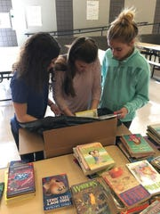 Left to right: Maggie Burns, Christa Bojczak and Angelea Riner begin to pack a box of books to ship to Africa.